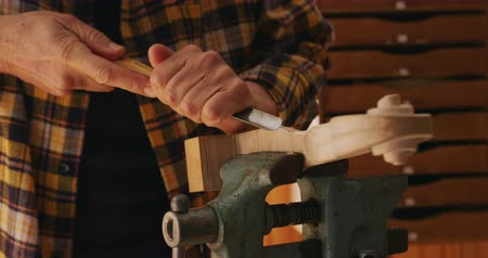 instrument maker : Front view mid section of a senior Caucasian female luthier working at a workbench in her workshop, using a chisel to shape a violin neck clamped in a vice Stock Footage