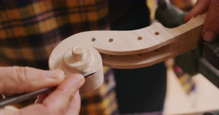 instrument maker : Close up of the hand of a senior Caucasian female luthier working on a violin at a workbench in her workshop, using a chisel to shape the scroll of a violin neck clamped in a vice, slow motion Stock Footage