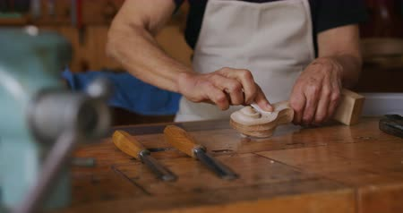 instrument maker : Front view mid section of a senior Caucasian female luthier wearing a white apron working on a violin at a workbench in her workshop, rubbing the scroll of a violin neck with a fine sandpaper, slow motion Stock Footage