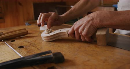 instrument maker : Side view mid section of a senior Caucasian female luthier working on a violin at a workbench in her workshop, rubbing the scroll of a violin neck with a fine sandpaper, slow motion