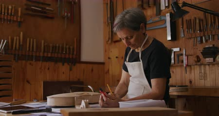 instrument maker : Side view of a senior Caucasian female luthier wearing a white apron making a violin at a workbench in her workshop, holding a compass and drawing with a pencil, tools hanging up on the wall in the background, slow motion