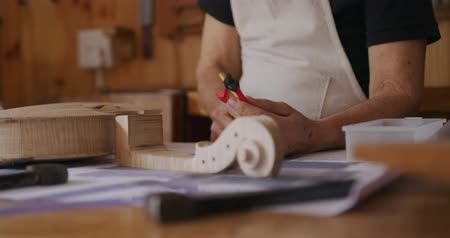 instrument maker : Front view mid section of a senior Caucasian female luthier wearing a white apron making a violin at a workbench in her workshop, holding a compass and drawing with a pencil, slow motion Stock Footage