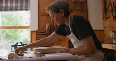 instrumenty : Side view of a senior Caucasian female luthier wearing a white apron working on a violin at a workbench in her workshop, making drawing with a pencil, parts of the unfinished violin lying on the workbench in front of her, slow motion Wideo
