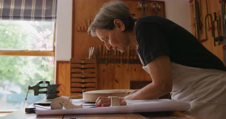 instrument maker : Side view of a senior Caucasian female luthier wearing a white apron working on a violin at a workbench in her workshop, making drawing with a pencil, parts of the unfinished violin lying on the workbench in front of her, slow motion Stock Footage