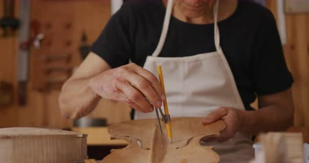 instrument maker : Front view close up of a senior Caucasian female luthier wearing a white apron working at a workbench in her workshop, using a pencil and a compass to draw on the inside of the front panel of a violin, slow motion Stock Footage