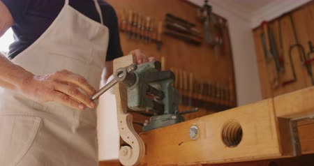 instrument maker : Low angle mid section of a senior Caucasian female luthier wearing a white apron making a violin at a workbench in her workshop, clamping the violin neck in a vice to work on it, slow motion