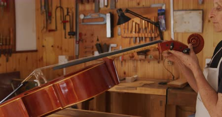 instrument maker : Side view of a senior Caucasian female luthier holding and inspecting a cello on the workbench at her workshop, with tools hanging up on the wall in the background.