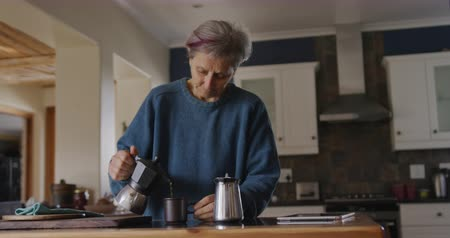 mindennapi : Front view of a senior Caucasian woman with short grey hair relaxing at home in her kitchen, standing at the counter making coffee, pouring coffee from a coffee pot into her cup, slow motion