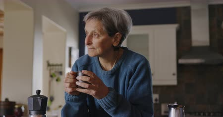 mindennapi : Front view of a senior Caucasian woman with short grey hair relaxing at home in her kitchen, leaning on the counter holding a cup of coffee, smiling and looking out of the window, slow motion