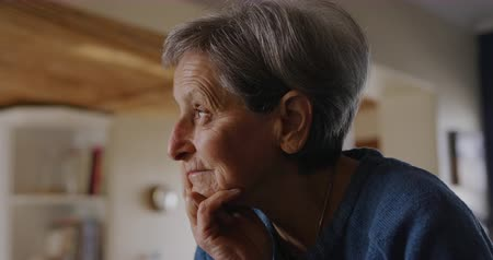 mindennapi : Side view close up of a senior Caucasian woman with short grey hair relaxing at home in her kitchen, leaning on the counter, looking out of the window and thinking, slow motion