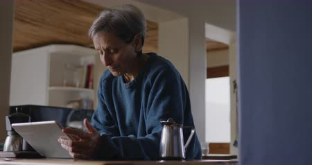 mindennapi : Side view of a senior Caucasian woman with short grey hair relaxing at home in her kitchen, leaning on the counter, using a tablet computer and concentrating, slow motion