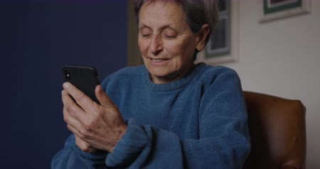 mindennapi : Front view close up of a senior Caucasian woman with short grey hair relaxing at home, sitting in an armchair, using a smartphone and smiling, slow motion