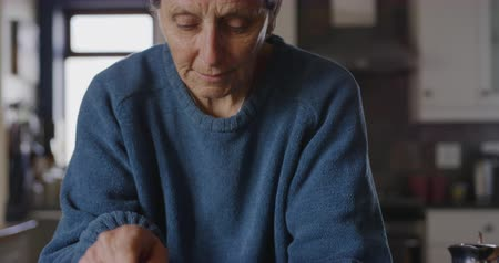 encimera : Front view close up of a senior Caucasian woman with short grey hair relaxing at home in her kitchen, leaning on the counter, using a tablet computer and concentrating, slow motion Archivo de Video