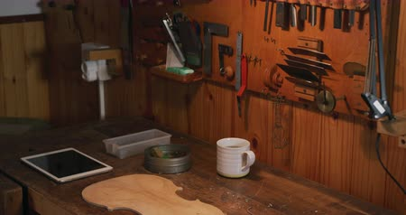 instrument maker : The workbench of a luthier in a workshop with the back of violin, a tablet computer and a coffee cup on it, and the tools of the trade hanging on the wall behind, slow motion