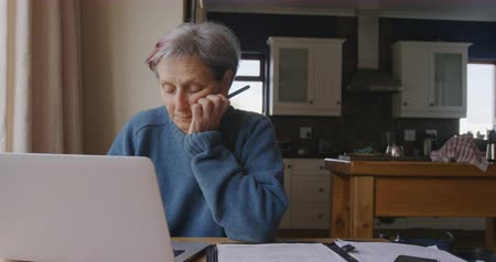 mindennapi : Front view of a senior Caucasian woman with short grey hair at home in her dining room, sitting at a table and using a laptop computer and concentrating, the kitchen in the background, slow motion