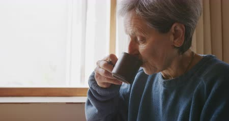 mindennapi : Side view close up of a senior Caucasian woman with short grey hair relaxing at home in her kitchen, sitting at a table by a window and drinking a cup of coffee, slow motion Stock mozgókép