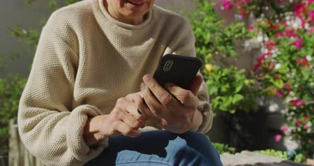 mindennapi : Front view close up of a senior Caucasian woman with short grey hair relaxing outdoors, sitting in her garden using a smartphone and laughing, slow motion