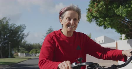independiente : Front view close up of a senior Caucasian woman with short grey hair wearing a red sweater sitting on a bicycle in the street, and smiling in the sun, slow motion