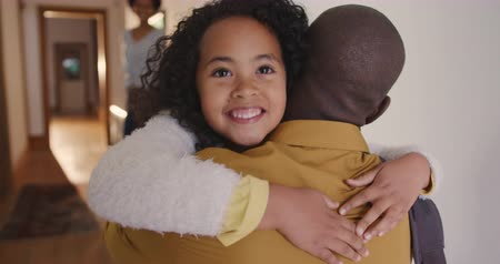 dark eyes : Rear view close up of an African American man arriving home, kneeling in the corridor and being hugged by his young daughter, who smiles facing the camera, looking over his shoulder, his wife visible standing in the background, slow motion Stock Footage
