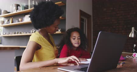 interessado : Side view of a young African American girl at home, sitting at a table with her mother looking at a laptop computer together, looking at each other and smiling, slow motion Vídeos