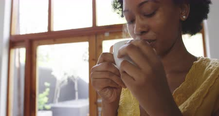 vaření v páře : Front view close up of an African American woman at home, standing in the kitchen drinking a steaming hot cup of coffee with eyes closed and smiling, slow motion