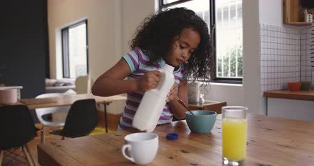 lids : Side view of a young African American girl at home in the kitchen, sitting at a table pouring milk from a bottle onto her breakfast cereal and putting the lid back on the bottle, slow motion