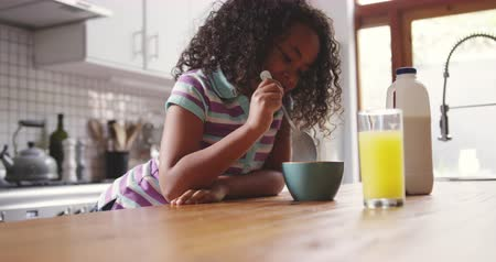 dark island : Side view of a young African American girl at home in the kitchen, sitting at the table with a bowl of breakfast cereal, mixing it with her spoon and smiling, a glass of orange juice on the table in front of her, slow motion