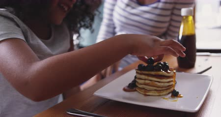 nalesniki : Side view close up of a young African American girl and her mother at home in the kitchen in the morning, sitting at the kitchen island, the picking a berry covered in syrup from her stack of pancakes and eating it, her mother laughing, slow motion