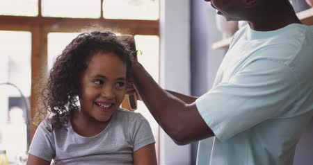 helping : Front view close up of a young African American girl at home in the kitchen, sitting in front of the window smiling while her father brushes and ties up her hair, slow motion Stock Footage
