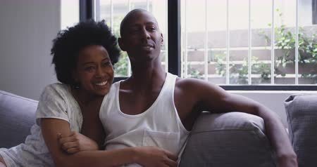 hazai room : Front view of an African American couple sitting together on the couch watching TV in their living room, turning to each other and smiling, slow motion