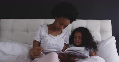racconto : Front view of an African American woman and her young daughter relaxing in the bedroom, sitting up in bed and reading a book together, slow motion