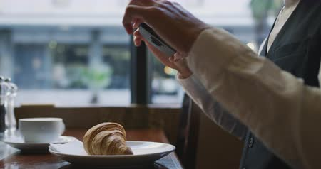 croissants : Side view of a young Caucasian elegant businessman in a cafe, taking photos of croissant with his smartphone, slow motion