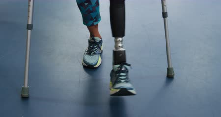 kule : Front view of a Caucasian woman with a prosthetic leg walking on crutches at a sports centre gym to make improvement