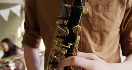 sassofono : Front view close up of a teenage musician boy standing playing a saxophone during a school band practice. He is focused Filmati Stock