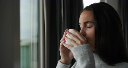 ruptura : Side view of young Caucasian woman enjoying time off, drinking coffee in the morning and looking out of the window