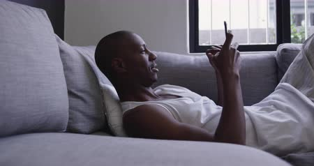 reclináveis : Side view of an African American man wearing a white vest reclining on a couch using a smartphone. He is laughing