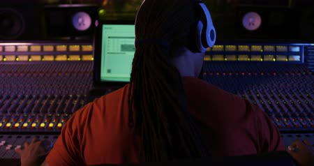 üreten : Rear view close up of a mixed race male sound engineer with long hair in a ponytail sitting and working at a mixing desk in a recording studio wearing headphones. Sound engineer working on producing a song