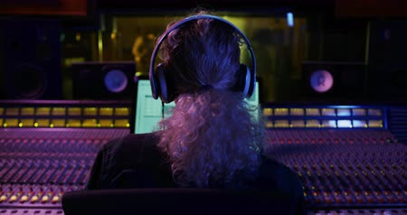 vocação : Rear view of a young Caucasian female sound engineer with blonde curly hair in a ponytail sitting and working at a mixing desk in a recording studio, putting on headphones and listening to music. Sound engineer working on producing a song