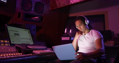vocacion : Front view of a mixed race male sound engineer sitting and working at a mixing desk in a recording studio wearing headphones and using a laptop computer. Sound engineer working on producing a song Archivo de Video