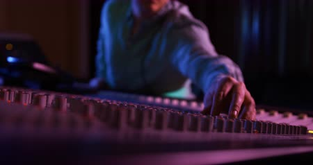 ajustando : Side view of a Caucasian male sound engineer sitting and working at a mixing desk in a recording studio wearing headphones, making adjustments, smiling and giving a thumbs up gesture. Sound engineer working on producing a song