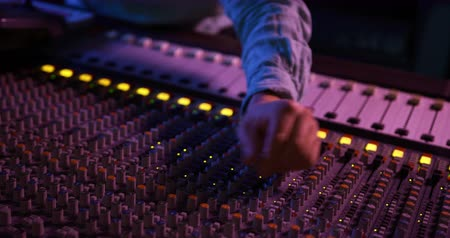 controles : Front view close up of the hand of a Caucasian male sound engineer making adjustments to the controls on a mixing desk while sitting and working in a recording studio. Sound engineer working on producing a song Archivo de Video