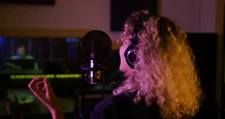 vokal : Rear view close up of a Caucasian female singer with blonde curly hair, wearing headphones, singing into a microphone and gesturing in a recording studio, the blurred figure of a sound engineer visible through a window in the background. Musicians working