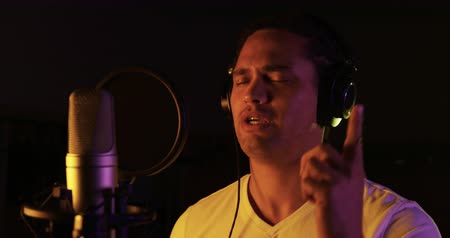 vocação : Front view close up of a mixed race male singer wearing headphones, singing or rapping into a microphone at a recording studio and gesturing with eyes closed. Musicians working on producing a song