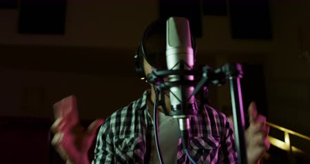 рэп : Front view of a mixed race male singer wearing headphones, singing or rapping into a microphone at a recording studio and gesturing. Musicians working on producing a song