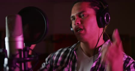 рэп : Front view close up of a mixed race male singer wearing headphones, singing or rapping into a microphone at a recording studio and gesturing. Musicians working on producing a song