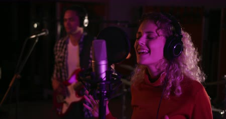 vokální : Front view of a Caucasian female singer with blonde curly hair, wearing headphones singing into a microphone at a recording studio, gesturing with her eyes closed, with a man playing electric guitar in the background. Musicians working on producing a song