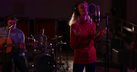 grão : Front view of a Caucasian female singer with blonde curly hair wearing headphones and singing into a microphone, a Caucasian male singer guitarist and a male drummer in the background, performing during a session at a recording studio. Musicians working o Stock Footage