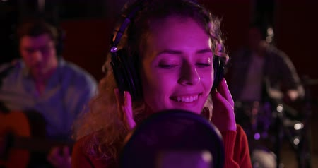 vokal : Front view close up of a Caucasian female singer with blonde curly hair wearing headphones and singing into a microphone, a Caucasian male guitarist and drummer playing in the background, during a session at a recording studio. Musicians working on produc Stok Video