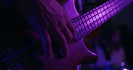 basgitaar : Front view mid section of a man playing bass guitar under a pink light during a session at a recording studio, with a Caucasian male drummer with long hair playing in the background . Musicians working on producing a song