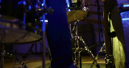 načasování : Low angle side view of a Caucasian man wearing headphones and playing a drum kit during a session at a recording studio. Musicians working on producing a song
